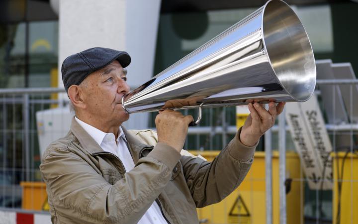Ein Mann steht auf der Straße mit einem silbernen Megafon