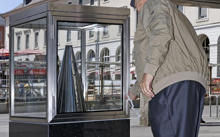 Ein Mann stellt ein silbernes Megafon zurück in eine Glasvitrine