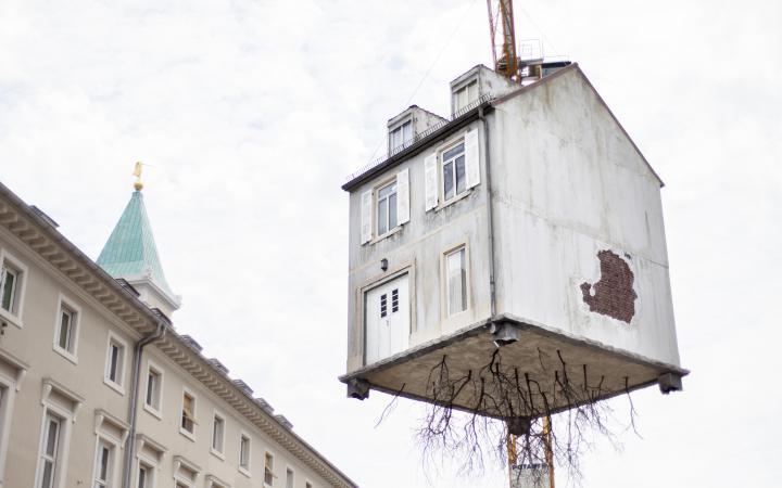 A house hangs on a crane