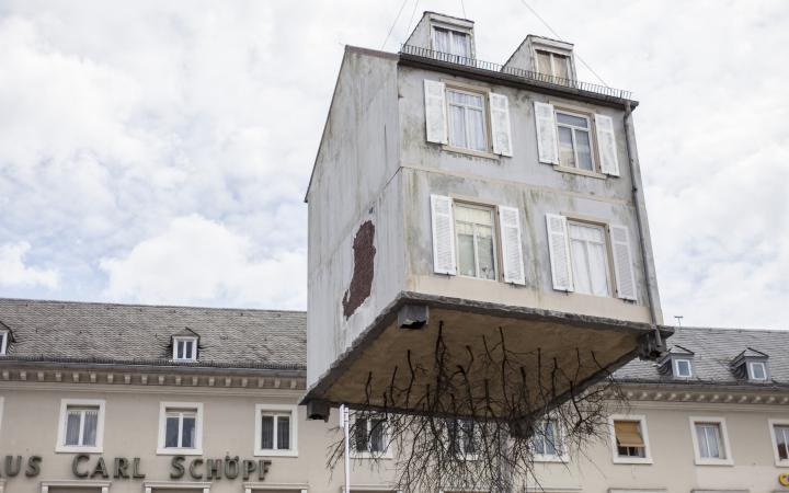 A house hangs on a crane
