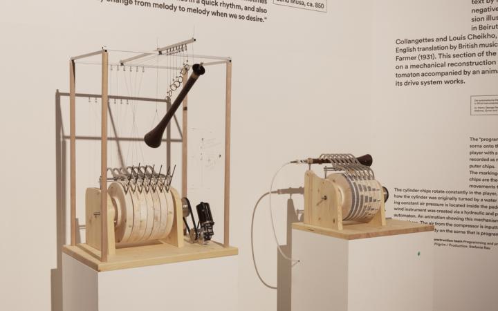 Zwei technische Geräte, überwiegend aus Holz und Metall, stehen jeweils auf einem Sockel.