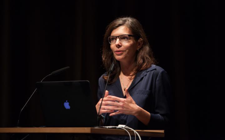 Eine Frau hält an einem Podium einen Vortrag.