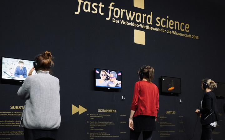 Three people with headphones on their ears look at different videos of the »fast forward science 2015« competition.