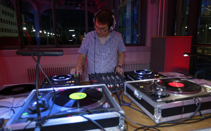 A man with microphones in front of a DJ set