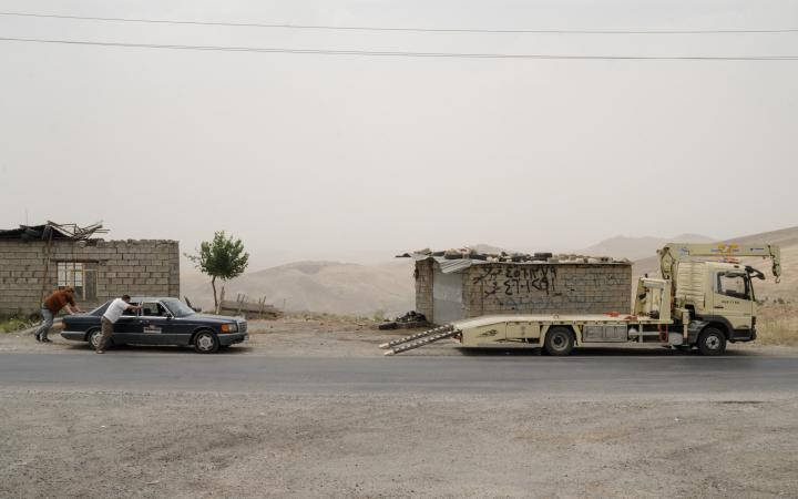 Two men are pushing a mercedes towards an tow truck. Behind them are ruinous buildings and a gaunt hilly landscape