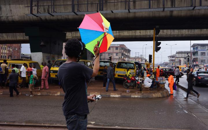 A man with a colorful umbrella records ambient noise on a busy street