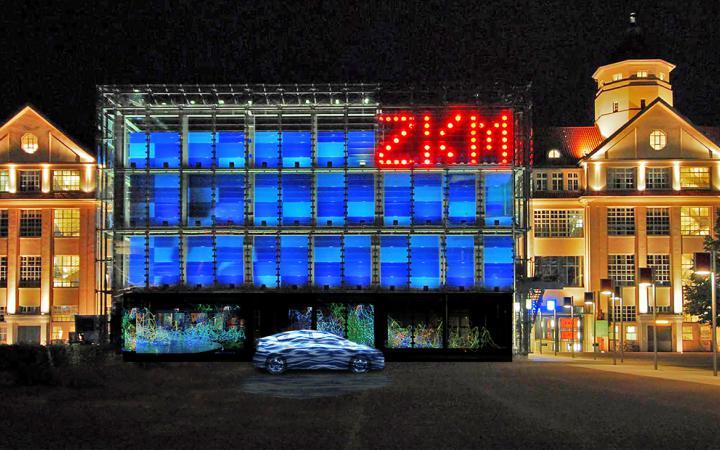 Ein Auto steht vor dem blauen Kubus. Rechts oben in großen, roten leuchtenden Lettern: ZKM
