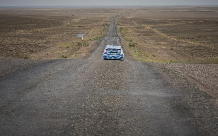 A blue car driving through a desert landscapes