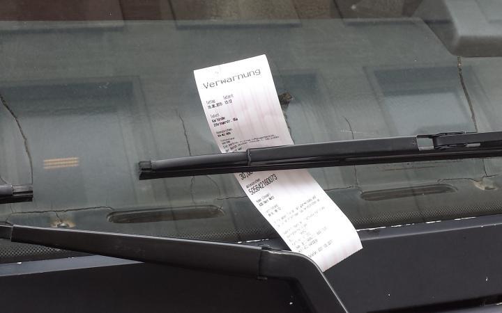 Nahaufnahmen von einem Strafzettel in der Windschutzscheibe eines roten Trucks