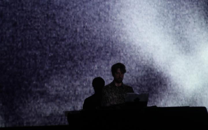 Mann auf der Bühne vor einem Laptop. Hintergrund ist in weißem Licht getaucht