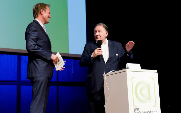 Two men talking to each other on stage