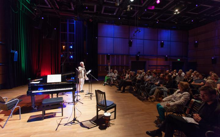Ein Mann steht auf der Bühne. Dort befinden sich mehrere Stühle und ein Klavier