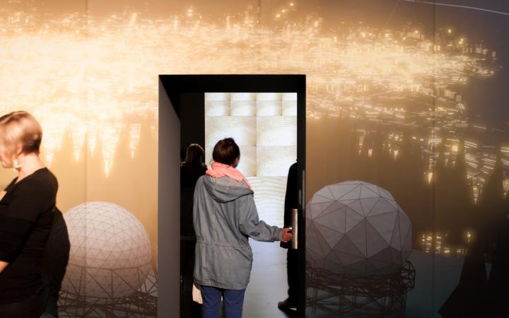 Eine Frau läuft durch eine Tür, auf der ein Video projiziert ist