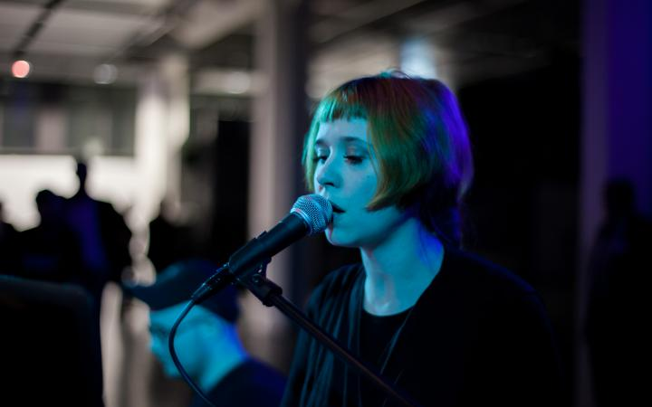 Singing woman at a microphone. The scene is lit by blue lights.