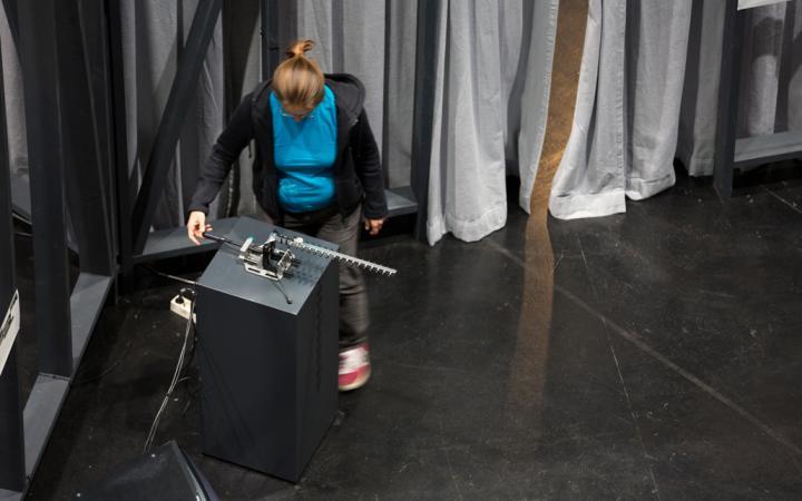 Eine Frau steht an einem Tisch und dreht an einem Gerät