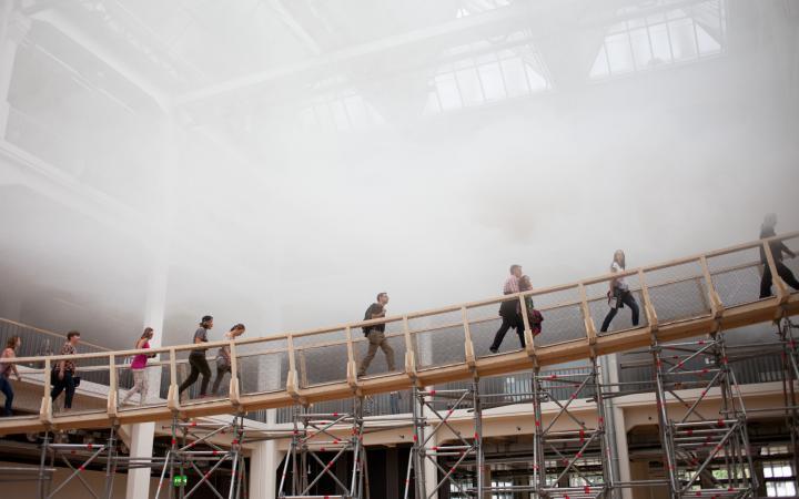 People walking on a ramp through fog