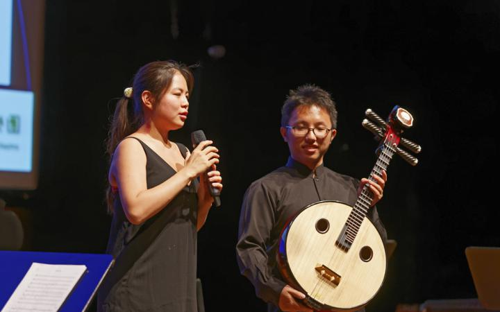 A woman with a microphone and a man with a kind of guitar