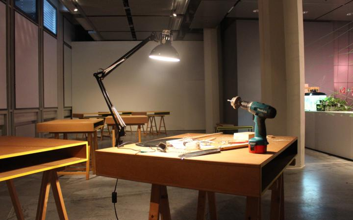 A wooden table on which a lamp and a drill stands