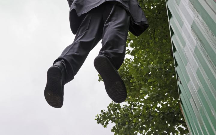 A man hanging in the air, holding himself with one hand.