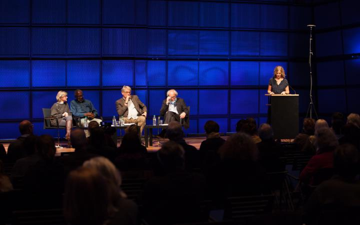 Four people sitting on a stage. Another person stands right by them on a pedestal and speak to the audience