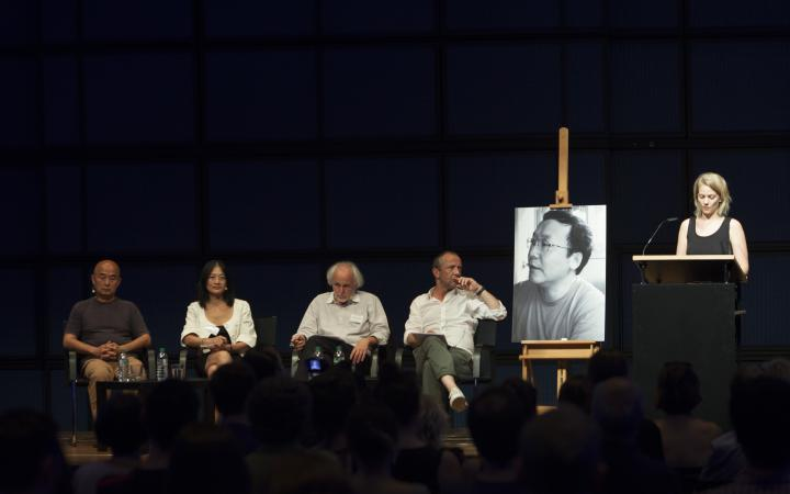 Four people sitting on the stage. At the lectern talking woman and a large black and white photo of a young man is placed.