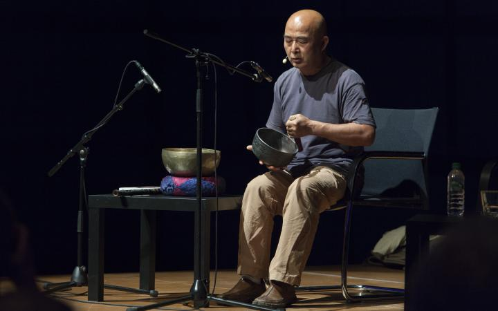 Ein Mann mit Klangschale auf der Bühne