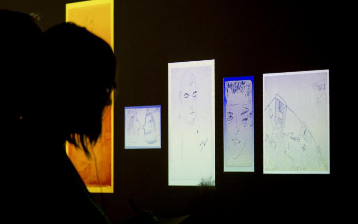 A person looks at enlightened drawings in the dark