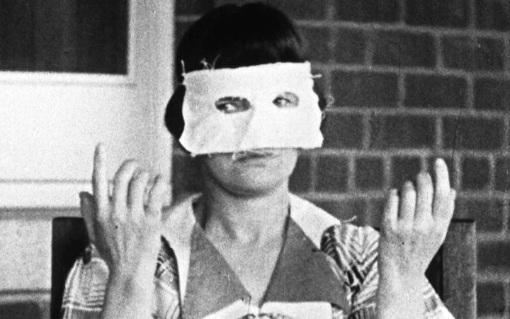A woman wearing a white eye mask