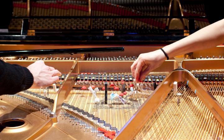 Zwischen Klaviersaiten werden Gegenstände gesteckt