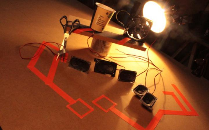 Various speaker boxes are illuminated by a desk lamp.
