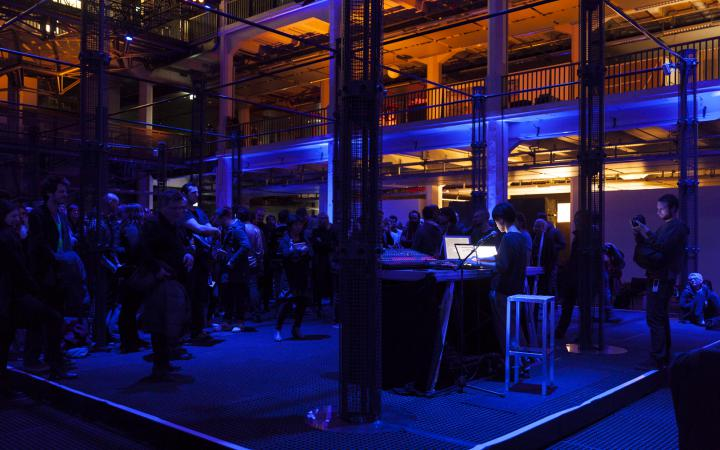 People stand and sit between illuminated speaker towers