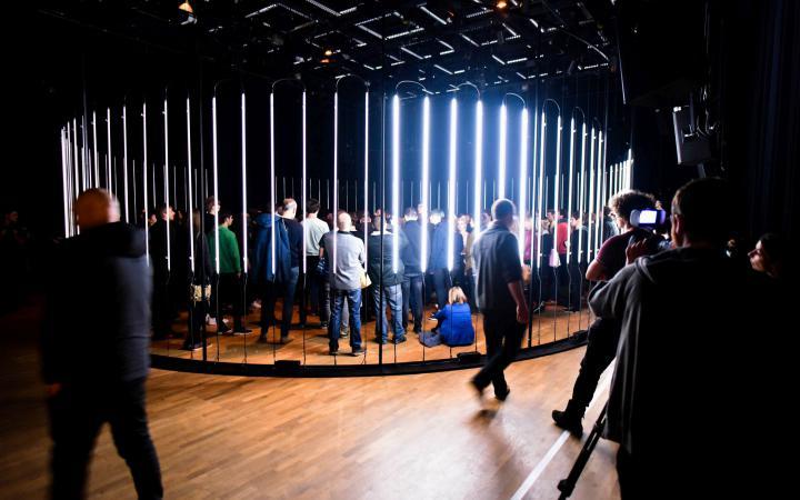 Ein Kreis aus leuchtenden Neonröhren, in dem viele menschen stehen