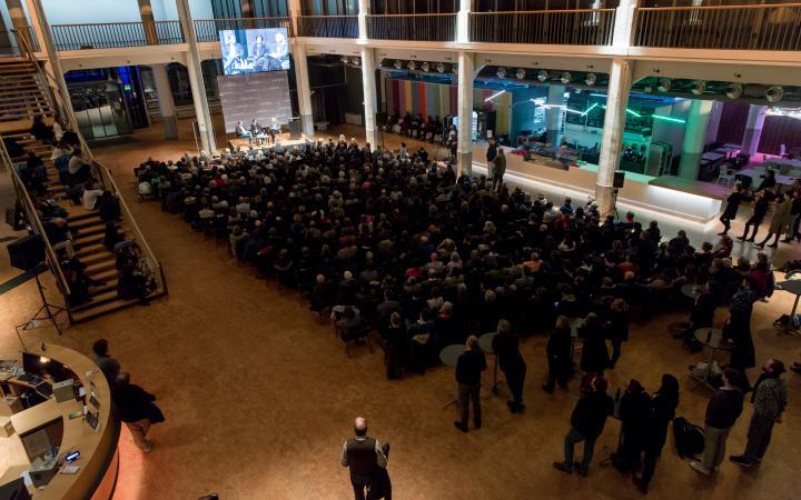 Menschen sitzen vor eine Bühne, über der eine große Leinwand hängt