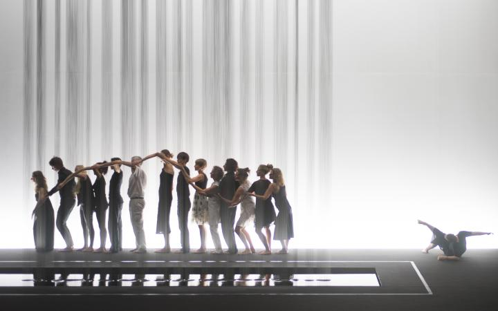 Performance with many people that are standing in a row and build a wave using their arms.
