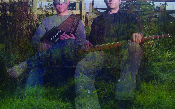 Two men are sitting on a meadow with musical instruments in their hands, their eyes are covered with silver tape
