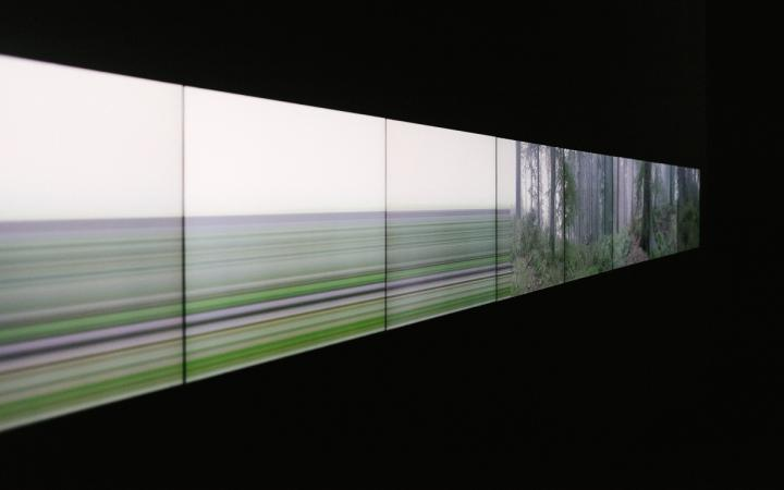 A screen on which a landscape disappears and merges into stripes