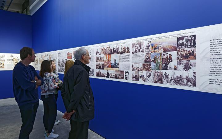 Fünf Menschen betrachten Bilder in einer Ausstellung, die auf blauem Grund hängen