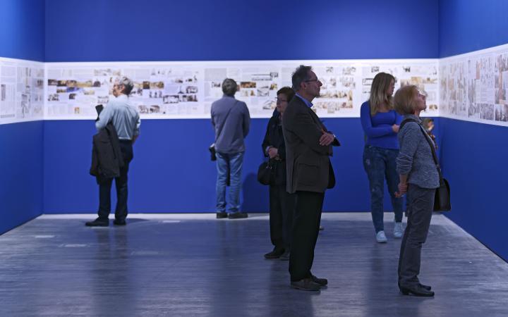 Menschen sehen sich Bilder der Ausstellung an, die auf blauem Hintergrund ausgestellt sind