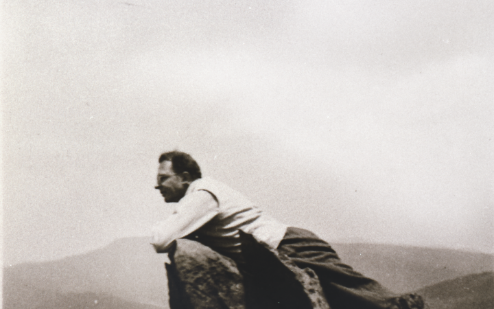 A man lying on a mountaintop, in the background you can see a mountain panorama