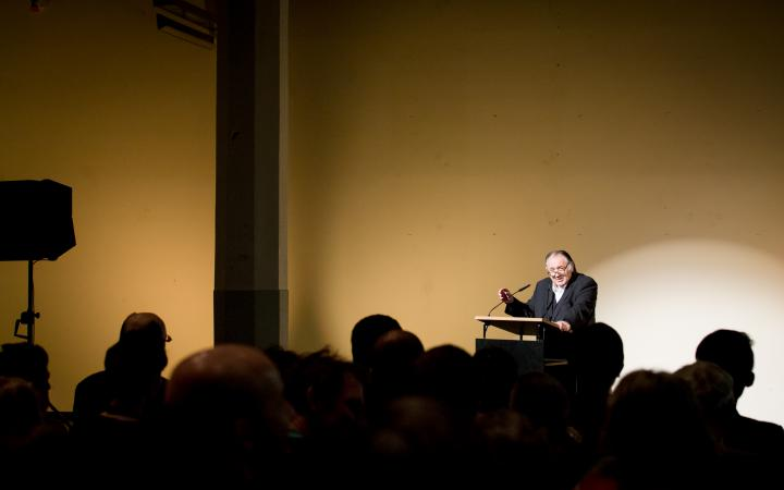 A man stands at a desk and talks to the audience