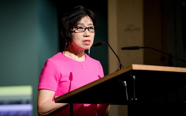 Eine Frau in pinkfarbenen Kleid spricht zum Publikum