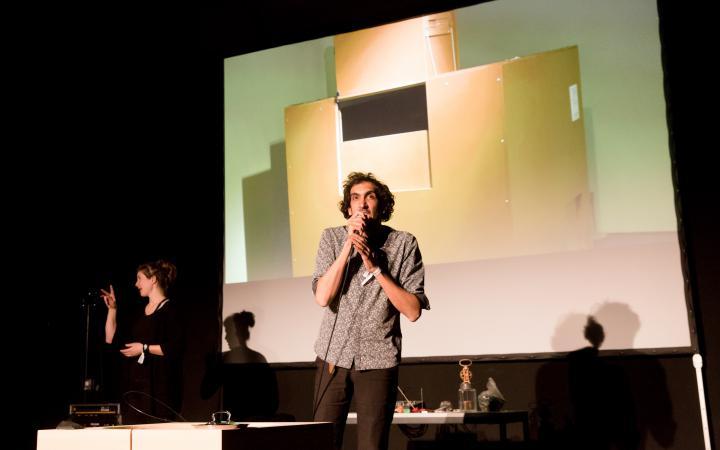 Ein Mann spricht in ein Mikrofon. Im Hintergrund ist eine Dolmetscherin für Gehörlose zu sehen
