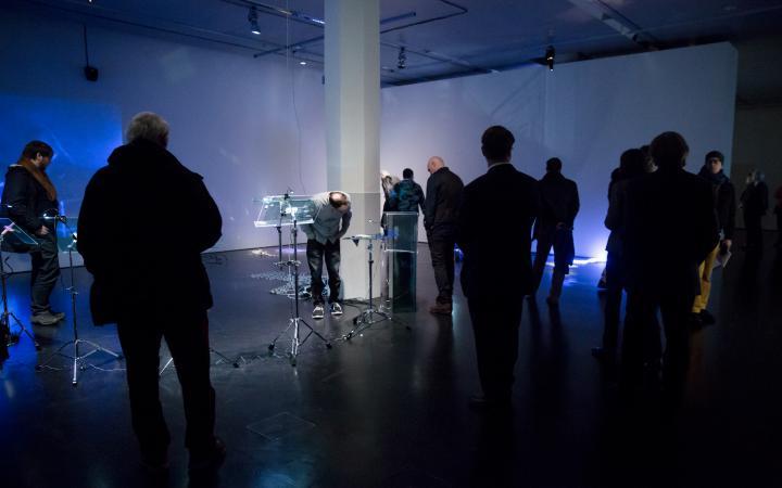 Menschen stehen in einem blauen Raum mit verschiedenen Gegenständen