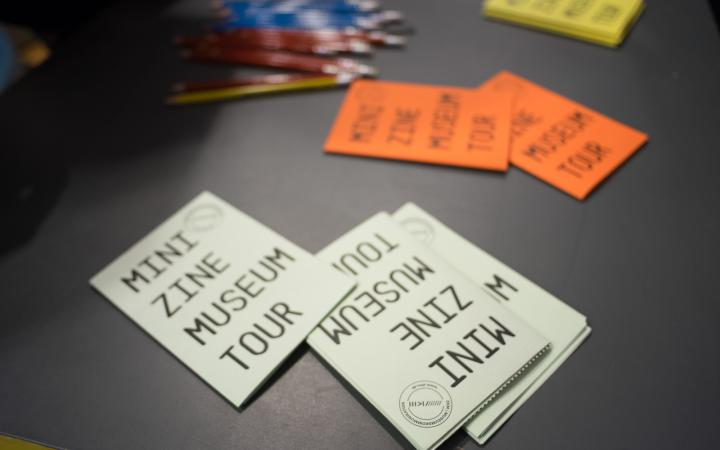"""Weiße und orange Handzettel, auf denen """"Mini tour"""" steht"""