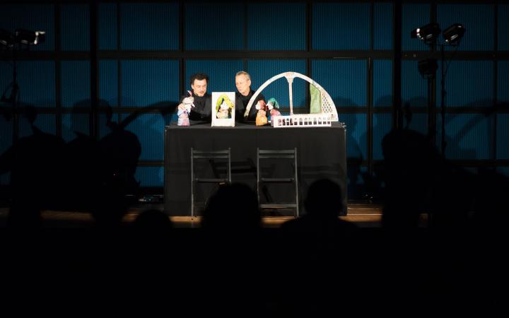 Zwei Männer spielen Puppentheater