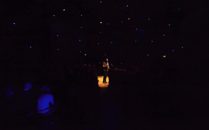 Ein Mann steht in einem dunklen Raum und spielt Trompete