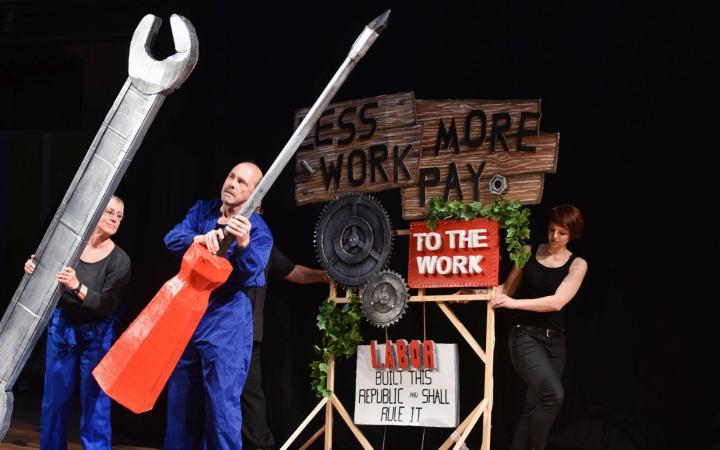 Drei Personen hantieren mit überdimensionalen Werkzeugen aus Pappmaché