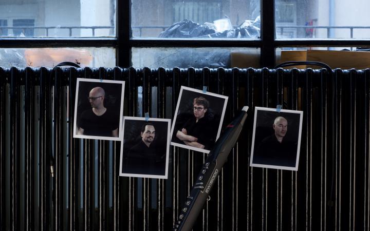 Vier Bilder von vier Männern kleben an einer Heizung. Dazwischen lehnt eine Klarinette.
