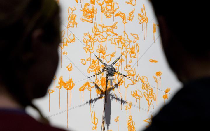 Two silhouettes looking at the computer-controlled robot painting with a yellow paint on a canvas.