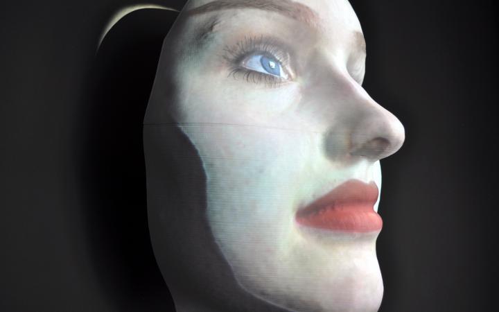 Das Bild zeigt ein maskenhaftes Gesicht, welches nach oben blickt.